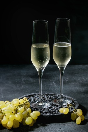 Two glasses of white champagne served on black wooden decorative board with green grapes over dark texture background. Copy space Imagens