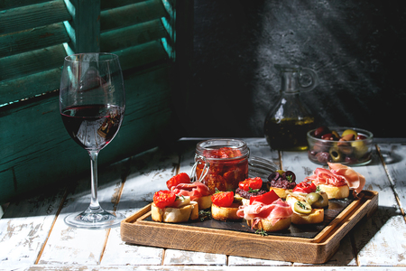 Tapas or bruschetta variety. Bread with ham prosciutto, sun dried tomatoes, olive oil, olives, pepper on slate wood board with glass of red wine over white table. Light via old jalousie. Rustic style.
