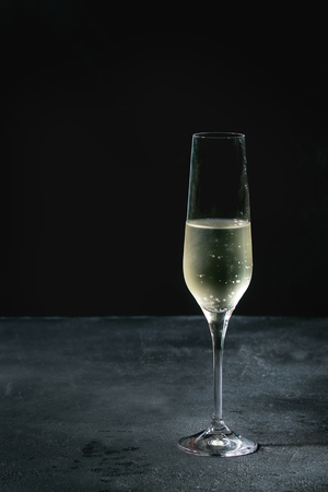 One glass of white champagne over dark texture background. Copy space