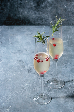 Two glasses of white champagne served with red berries and rosemary over blue texture background. Copy space 版權商用圖片