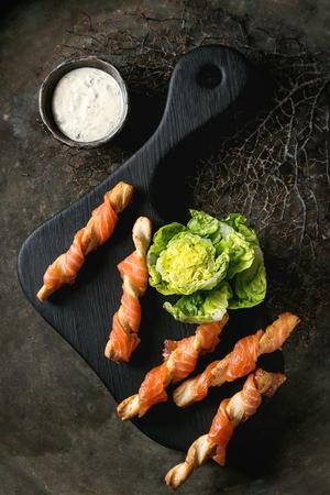 Voorgerecht met gerookte zalm op knapperige breadsticks geserveerd op zwarte portie bord met kaas dille saus, zeezout en groene salade op oude donkere achtergrond. Bovenaanzicht met ruimte