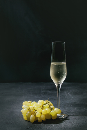 One glass of white champagne with green grapes over dark texture background. Copy space