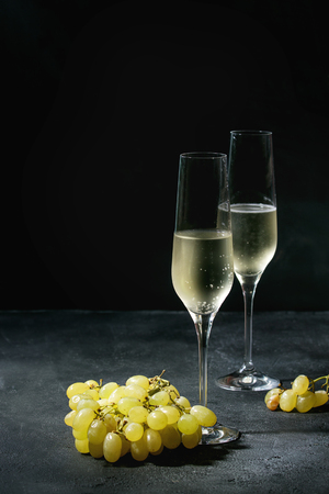 Two glasses of white champagne served with green grapes over dark texture background. Copy space Stock Photo
