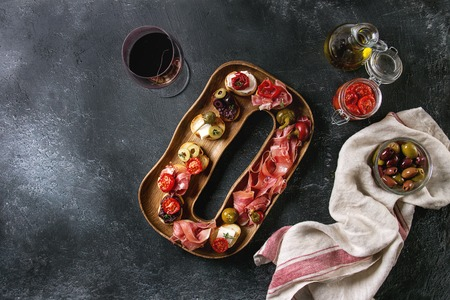 Tapas or bruschetta variety. Bread with ham prosciutto, sun dried tomatoes, olive oil, olives, pepper on decorative wood plate with glass of red wine over dark texture background. Top view with space