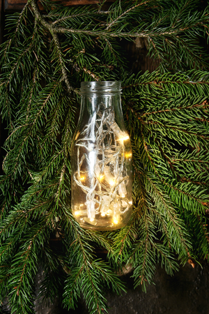 christmas lights garland in glass bottle on green fir tree branches over dark texture background