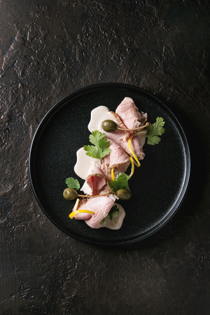 Vitello tonnato italian dish. Thin sliced veal with tuna sauce, capers and coriander served on black plate over dark texture background. Top view, copy space Banco de Imagens