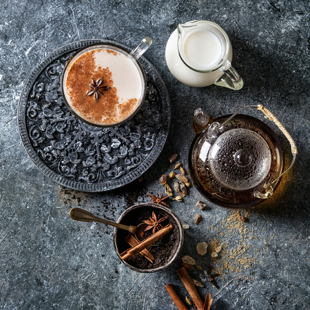 Glass cup of traditional indian masala chai tea with ingredients above. Cinnamon, cardamom, anise, sugar, black tea in glass teapot, jug of milk over dark texture background. Top view, space. Square image