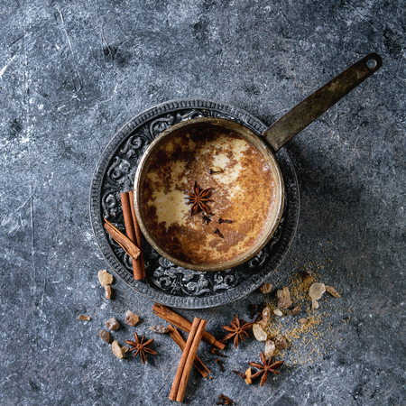 Vintage pot of traditional indian masala chai tea with ingredients above. Cinnamon, cardamom, anise, sugar over dark texture background. Top view with copy space. Square image