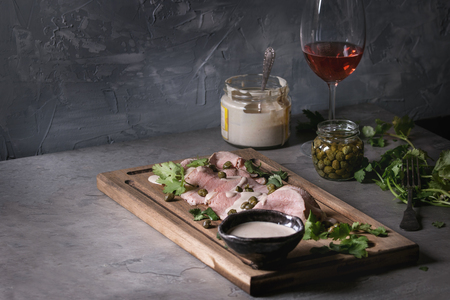 Vitello tonnato italian dish. Thin sliced veal with tuna sauce, capers and coriander served on wooden serving board, glass of rose wine and ingredients above over gray texture kitchen table.