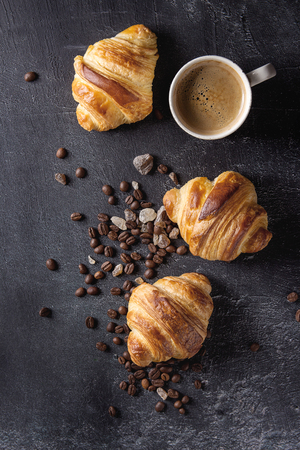 Des croissants traditionnels fraîchement cuits au four et une tasse de café espresso, grains de café, sucre sur fond de texture noire. Vue de dessus, espace de copie Banque d'images - 93378896