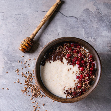 Bowl of milk cereal porridge with additives flax seeds, chocolate and berries over gray kitchen table. Top view with space. Square image Stock Photo