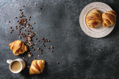 Des croissants traditionnels fraîchement cuits au four sur une assiette vintage blanche et une tasse de café espresso, grains de café, sucre sur fond de texture noire. Vue de dessus, espace de copie Banque d'images - 93378906