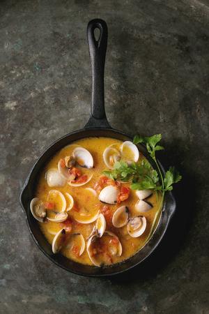 Vongole in tomatenroomsaus voor pasta in gietijzeren pan op oude metalen textuur achtergrond. Bovenaanzicht, ruimte