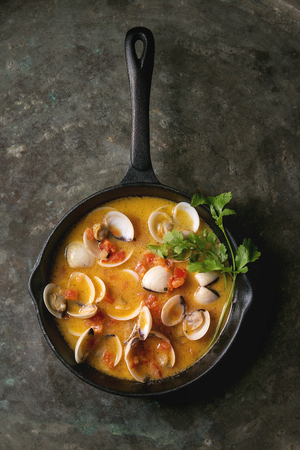 Vongole in tomato cream sauce for pasta in cast-iron pan over old metal texture background. Top view, space Stock Photo