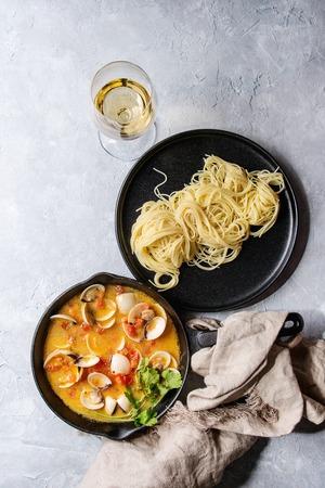 Vongole in tomatenroomsaus voor pasta in gietijzeren pan met textiel, glas witte wijn en zwarte plaat gekookte spaghetti over grijze textuurachtergrond. Bovenaanzicht, ruimte