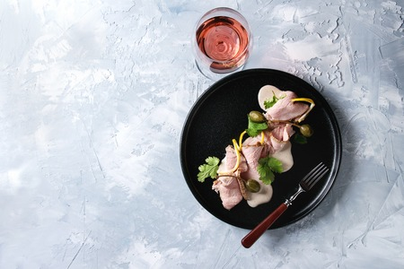 Vitello tonnato italian dish. Thin sliced veal with tuna sauce, capers and coriander served on black plate with fork and glass of rose wine over gray texture background. Top view, space Standard-Bild - 93378770