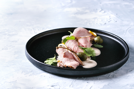 Vitello tonnato italian dish. Thin sliced veal with tuna sauce, capers and coriander served on black plate over gray texture background.