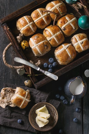 Hot cross buns in wooden tray served with butter, knife, blueberries, easter eggs, birch branch, jug of cream on textile napkin over old texture wood background. Top view, space. Easter baking. Stock Photo - 93378781