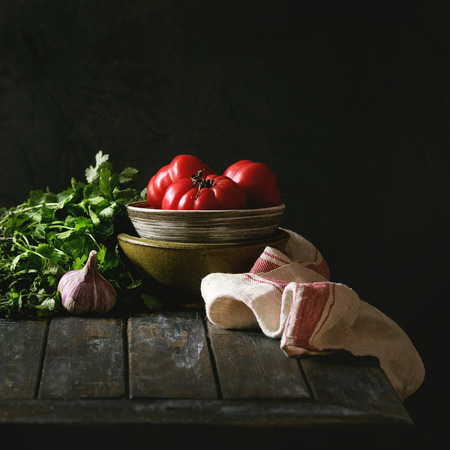 Bowl of tomatoes with herbs, garlic and linen towel on old wooden kitchen table. Dark rustic still life. Square image