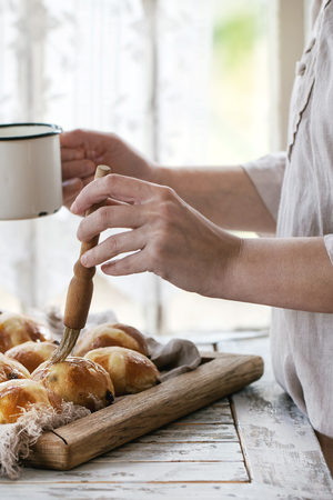 Homemade Easter traditional hot cross buns on wooden tray with textile over white wooden table. Window at background. Female hands cover with syrup. Natural day light. Rustic style.