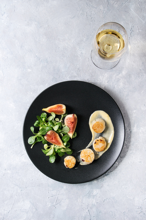 Fried scallops with lemon, figs, sauce and green salad served on ceramic black plate with glass of white wine over gray texture background. Top view, space. Plating, fine dining Stock Photo