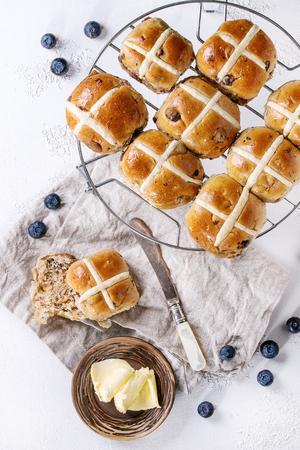 뜨거운 십자가 빵을 베이킹 랙 버터, 신선한 블루 베리, 나이프와 크림 화이트 이상 섬유 냅킨에 용기와 함께 제공 텍스처 콘크리트 배경입니다. 상위