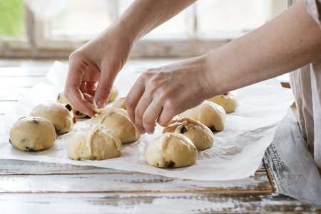 Raw unbaked buns. Ready to bake homemade Easter traditional hot cross buns on baking paper over white wooden table. Window at background. Female hands make a cross. Natural day light. Rustic style. Banco de Imagens - 93949058