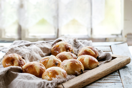 Homemade Easter traditional hot cross buns on wooden tray with textile over white wooden table. Window at background. Natural day light. Rustic style.