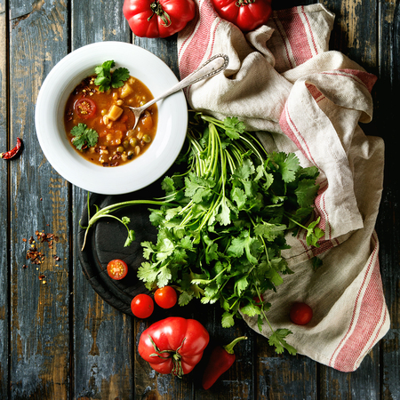 Vegetarian hot carrot tomato pea potato soup, served in white plate with fresh coriander and tomatoes on kitchen towel over old wooden plank table. Top view with space. Square image Stock Photo
