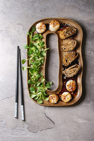 Asian style fried scallops with Japanese Rolled Omelette Tamagoyaki and soy sesame sauce in wooden plate with green salad, chopsticks over gray texture background. Top view, space