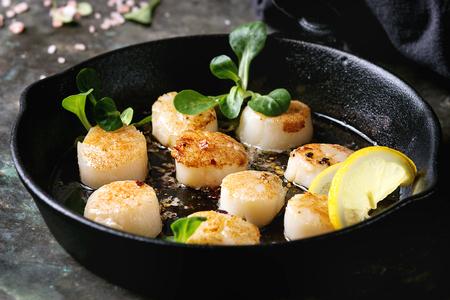 キャストアイロン鍋にバターレモンスパイシーソースを添えたホタテの揚げ物は、古いダークメタルの背景にグリーンサラダとテキスタイルナプキ
