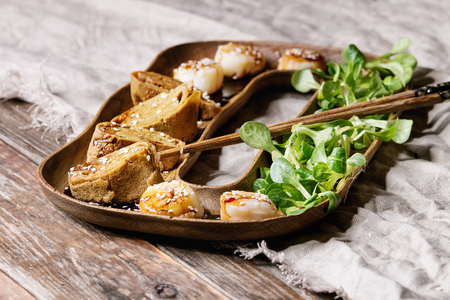 Asian style fried scallops with Japanese Rolled Omelette Tamagoyaki and soy sesame sauce in wooden plate with green salad, chopsticks over textile linen background. Close up