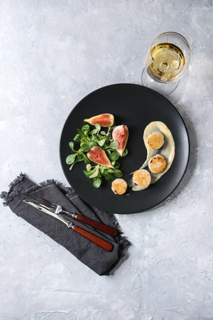 Fried scallops with lemon, figs, sauce and green salad served on black plate with glass of white wine and cutlery over gray texture background. Top view, space. Plating, fine dining Stock Photo