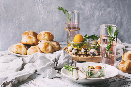 Easter table setting with colored orange eggs, hot cross buns, green branches decorated, empty white plate with cutlery, glass of lemonade drink over white plank wooden table with textile tablecloth.