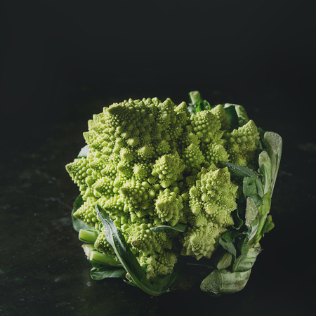 Fresh raw organic cabbage romanesco over dark texture background. Imagens