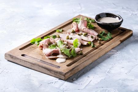 ヴィテッロ・トナトのイタリア料理。マグロソース、ケッパー、コリアンダーを使った薄切り卵は、灰色のテクスチャーの背景の上に木製のサービ 写真素材