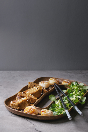 Asian style fried scallops with Japanese Rolled Omelette Tamagoyaki and soy sesame sauce in wooden plate with green salad, chopsticks over gray texture table. Copy space 版權商用圖片