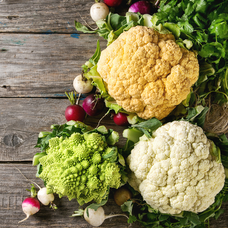 Variety of fresh raw organic colorful cauliflower, cabbage romanesco and radish with bundle of coriander over old wooden background. Top view with copy space. Food market concept. Square image Imagens