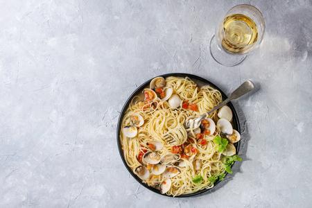 파스타 스파게티 포크와 회색 질감 배경 위에 화이트 와인의 유리 검정 잉크 판에 토마토 크림 소스에 Vongole. 상위 뷰, 복사본 공간
