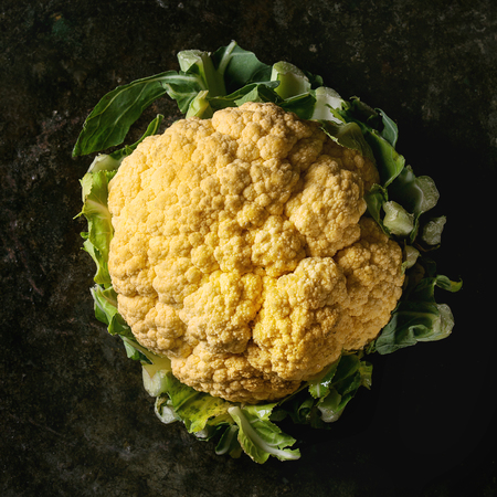 Fresh raw yellow organic cauliflower, cabbage romanesco over dark texture background. Top view with space. Healthy eating concept. Square image Imagens