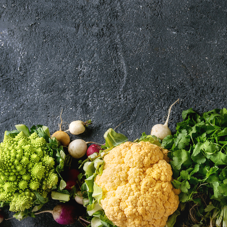 Variety of fresh raw organic colorful cauliflower, cabbage romanesco and radish with bundle of coriander over dark texture background. Top view with copy space. Healthy eating concept. Square image Banco de Imagens