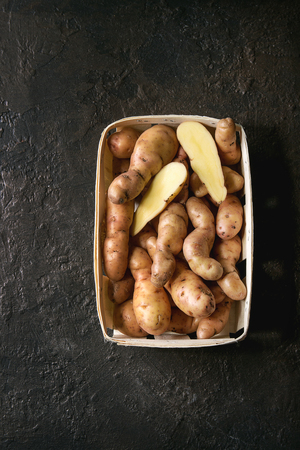 Raw uncooked organic potatoes named bayard, whole and slice, in market baskets over dark texture background. Top view, copy space