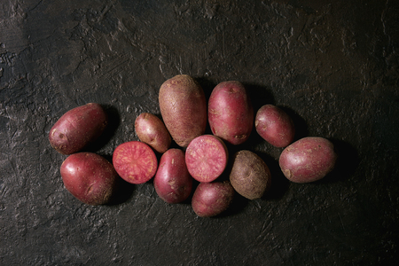 Raw uncooked organic potatoes named lilu rose, whole and slice over dark texture background. Top view, copy space