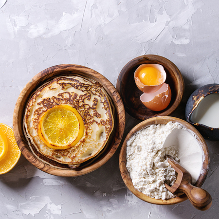 Homemade pancakes with fried orange and ingredients above. Wooden bowls of flour, yolk, salt, milk, olive oil over gray texture background. Top view with space. Home cooking concept. Square image