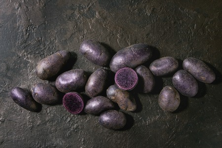 Raw purple uncooked organic potatoes named prunelle, whole and slice over dark texture background. Top view, copy space Banco de Imagens