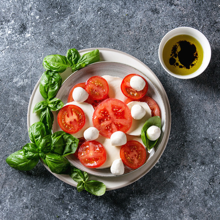 Italian caprese salad with sliced tomatoes, mozzarella cheese, basil, olive oil. Served in ceramic plate over gray texture background. Top view with copy space. Restaurant menu. Square image