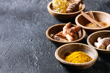 Ingredients for turmeric latte. Ground turmeric, curcuma root, cinnamon, ginger, honeycombs in wooden bowls over black texture background. Close up, copy space Standard-Bild - 95049624
