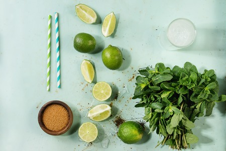 Ingredients for making mojito cocktail. Bundle of fresh mint, limes, brown sugar, crashed ice cubes, glass of soda water, cocktail tubes over green pin up background. Top view, space. Food knolling