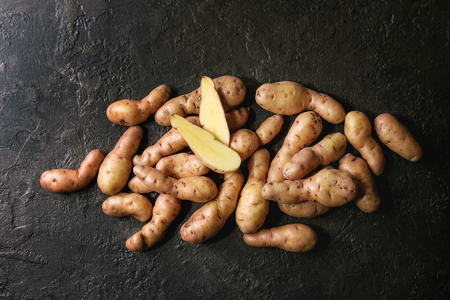 Raw uncooked organic potatoes named bayard, whole and slice over dark texture background. Top view, copy space Banco de Imagens