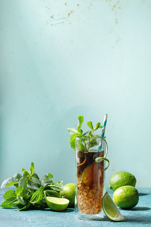 Glass of classic Cuba libre cocktail with lime, mint, crushed ice and cola, served with ingredients above and retro cocktail tubes over turquoise green pin-up style background. Sunlight, copy space